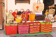 Street market merchant's stall with colourful shopping baskets, A market street in the old town Sanary Var Cote d'Azur France