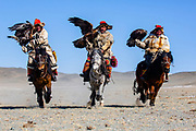 Three Kazakh eagle hunters hunting in the Altai mountains with their golden eagles on horseback, Altai Mountains, Bayan Ulgii, Mongolia