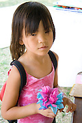 Young Asian girl age 6 holding a pink and blue paper flower. Dragon Festival Lake Phalen Park St Paul Minnesota USA