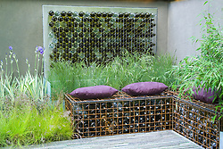 Courtyard garden with bottle water feature, bottle-filled gabions and planting of grasses and iris. Simon's Garden with Va Va Voom. Design: Scenic Blue Design Team - Chelsea 2005