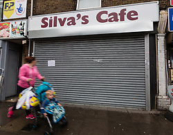© Licensed to London News Pictures. 24/09/2014. Edmonton, UK. A woman walks past Silva's cafe in Church Street, Edmonton, which is closed today and a notice posted on the shutter notifying customers of Palmira Silva's funeral which takes place today. Palmira Silva, a grandmother who was killed by a machete in her back garden used to work at Silva's Cafe. Photo credit : Vickie Flores/LNP