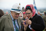 A man in a pith helmet looking at a woman's phone before the start of Pipefest Stirling, an event staged at Stirling Castle to coincide with the 700th anniversary of the Battle of Bannockburn. The event was attended by 1600 pipers, Highland dancers and other musicians and formed a procession through the city's streets. The Battle of Bannockburn took place in 1314 and resulted in the defeat of Edward II's English army by the Scots under Bruce.