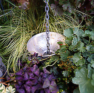 water is captured into an underground holding tank by using a rain chain and the cover for a clamp light.  A fine example of low cost materials for water saving at home.