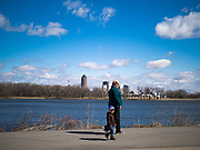 """29 MARCH 2020 - DES MOINES, IOWA: People walk around Gray's Lake, a popular park and lake near downtown Des Moines, with the city skyline on the other side of the lake. On Sunday morning, 29 March, Iowa reported 336 confirmed cases of the Novel Coronavirus (SARS-CoV-2) and COVID-19. There have been four deaths attributed to COVID-19 in Iowa. Restaurants, bars, movie theaters, places that draw crowds are closed until 07 April. The Governor has not ordered """"shelter in place""""  but several Mayors, including the Mayor of Des Moines, have asked residents to stay in their homes for all but the essential needs. People are being encouraged to practice """"social distancing"""" and many businesses are requiring or encouraging employees to telecommute.        PHOTO BY JACK KURTZ"""