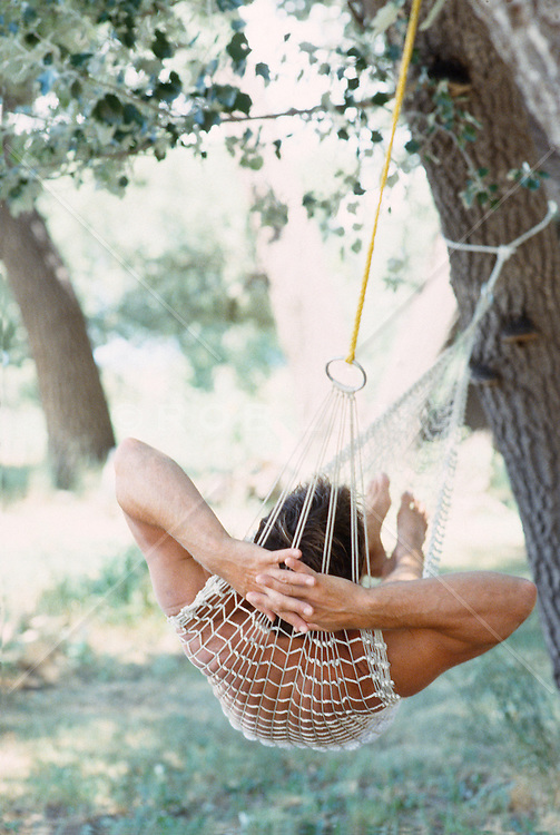 Back of man with arms behind head relaxing in a tree hammock