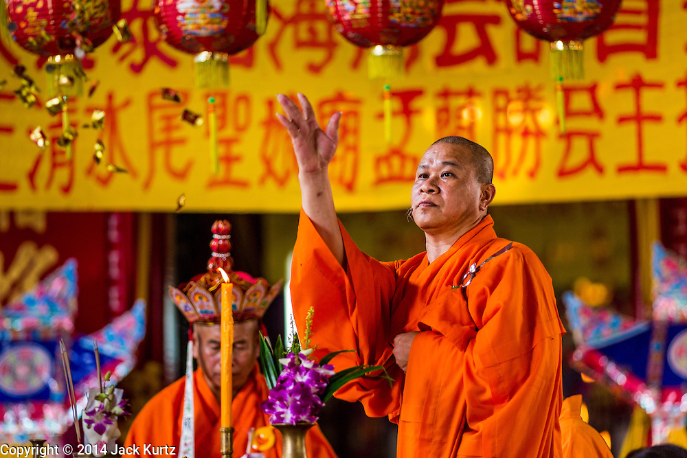 """09 AUGUST 2014 - BANGKOK, THAILAND:  A Vietnamese Mahayana Buddhist monk throws candies to the crowd during a Ghost Month service at the Ruby Goddess Shrine in the Dusit section of Bangkok. The seventh month of the Chinese Lunar calendar is called """"Ghost Month"""" during which ghosts and spirits, including those of the deceased ancestors, come out from the lower realm. It is common for Chinese people to make merit during the month by burning """"hell money"""" and presenting food to the ghosts. At Chinese temples in Thailand, it is also customary to give food to the poorer people in the community.        PHOTO BY JACK KURTZ"""