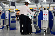Departing passenger use British Airways self-service check-in kiosks at Heathrow Airport's Terminal 5.
