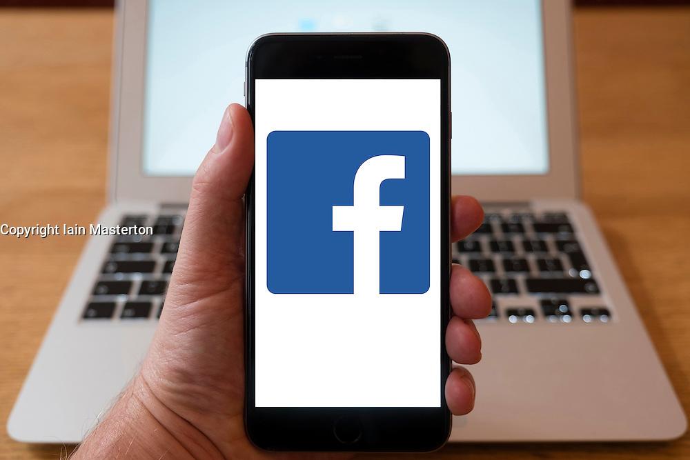 Using iPhone smartphone to display logo of Facebook social media website