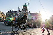 In Amsterdam rijdt een jongen op de fiets over de Dam bij het koninklijk paleis.<br /> <br /> In Amsterdam is riding his bike on the Dam square as a woman is crossing.