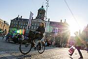 In Amsterdam rijdt een jongen op de fiets over de Dam bij het koninklijk paleis.<br /> <br /> In Amsterdam is riding his bike on the Dam square as a woman is crossing.