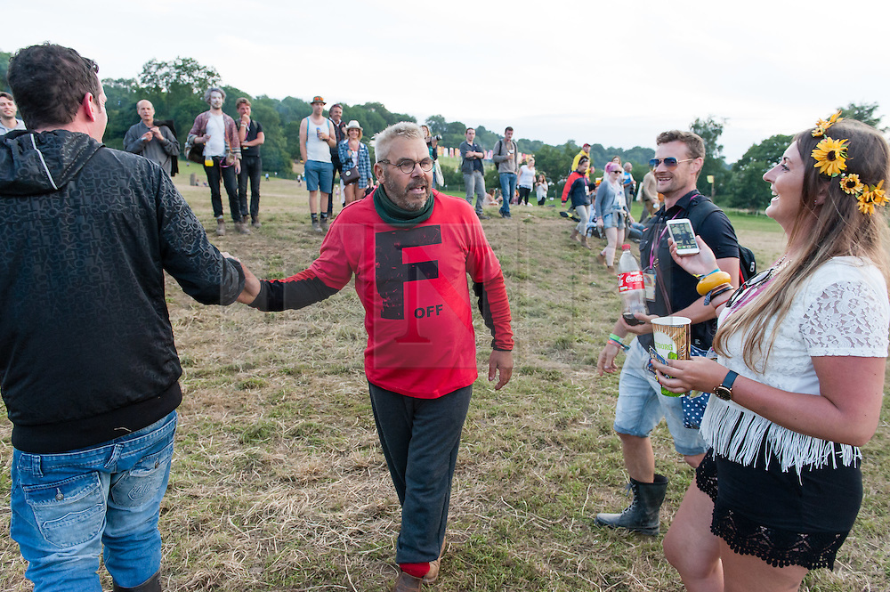 © Licensed to London News Pictures. 27/06/2015. Pilton, UK.  A man jumps the Glastonbury Festival wall without a ticket by flying into the festival in a light propellor-driven motorised aircraft, landing in next to the Stone Circle at 9pm to cheers from the watching festival goers.  Festival officials were quick on scene, after a tug-of-war with the wall jumper (helped by nearby festival goers) and the aircraft, they confiscate the aircraft but allowing the man to walk free.  The wall jumper receives congratulatory hugs by festival goers.  The wall jumper when asked for a quote by the photographer the man said 'I need a beer'.  This years headline acts include Kanye West, who is due onstage later his evening, The Who and Florence and the Machine, the latter being upgraded in the bill to replace original headline act Foo Fighters. Photo credit: Richard Isaac/LNP
