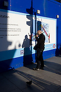 A man licks his thump after a eating a cake in front of a London Crossrail construction site hoarding.