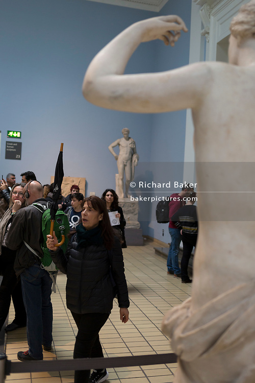 A tour leader takes her group past Greek and Roman sculpture in the British Museum, on 11th April 2018, in London, England.