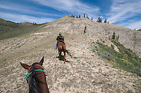 Andy Camp rides along a ridgeline near his ranch near the Upper Gros Vente River in mid-June. Camp, who has been a hunting outfitter and guide in the area, said he's seen the hillside rise and bulge about 100 feet during the last several years, and vegetation has slowly died away from supposed thermal activity.