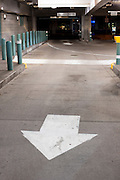 A white arrow painted on the gound in a downtown parking garage leads the traffic in the right direction. Missoula Photographer