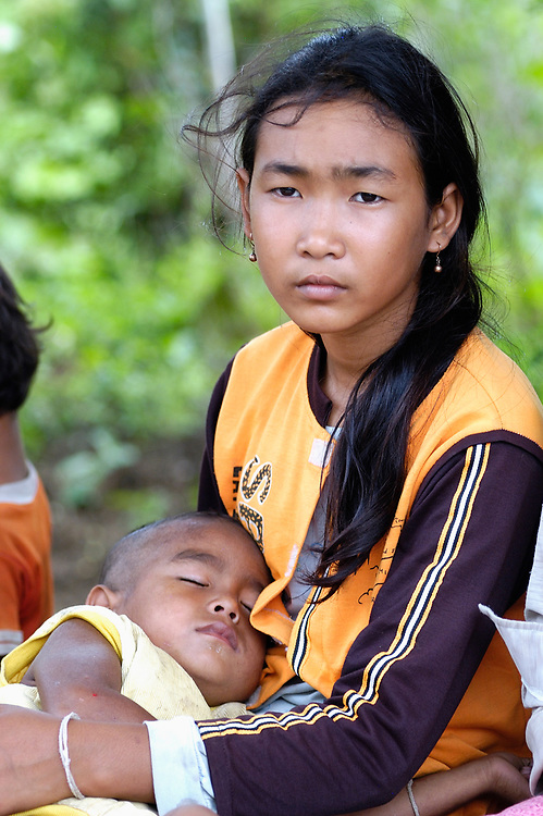 Bou Kim Heng holds her little brother, Bou Kim Heng. Both are HIV positive AIDS orphans, part of a support group of people living with HIV/AIDS in the Cambodian village of Khlang Meas. The group receives support from Catholic Relief Services.