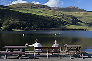 Visitors sit overlooking (Lake) Tal-Y-Llin and in the distance, the 2,928ft mountain Cader Idris, on 12th September 2018, near Dolgellau, Gwynedd, Wales.