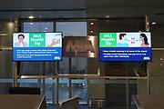 Monitors with COVID-19 health advisory notices atTerminal D of the Miami International Airport, Saturday, Feb. 13, 2021, in Miami.