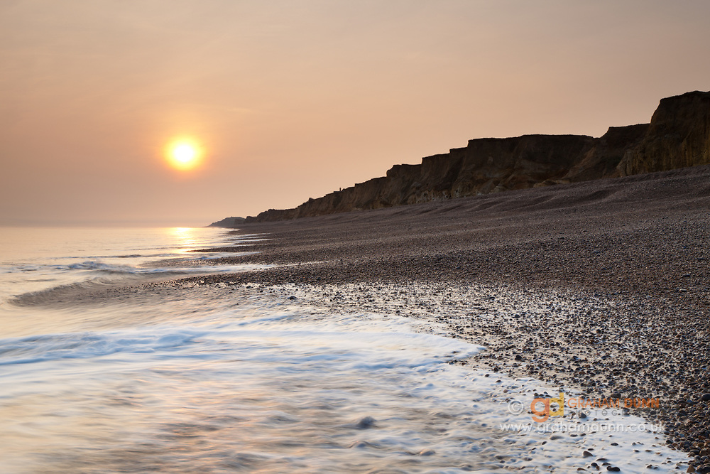 The morning sun breaks through hazy skies above Weybourne beach and cliffs. North Norfolk, East Anglia.