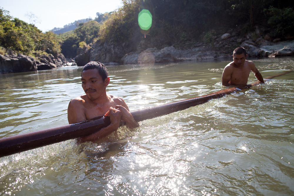 Rio Blanco. Lenca indigenous men retrieve part of a bridge that they have rebuilt several times after the police destroy it. At this point in the river, which is sacred to the Lenca people, a hydroelectric dam is proposed and heavily fought against by the Lenca people. Berta Cáceres was assassinated while she led the struggle against the dam, and several other leaders and members of the same organisation have been attacked and killed.
