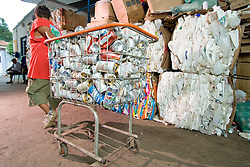 Pessoa trabalhando na reciclagem de latas de aluminio em cooperativa / People working in aluminium can recycling at one co-operative