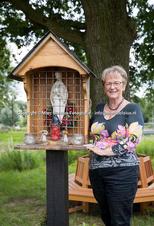 Nederland,  Boxtel, Diny Stolvoort in de tuin bij de Walnoot bij het nieuwe mariabeeldje en zitje.