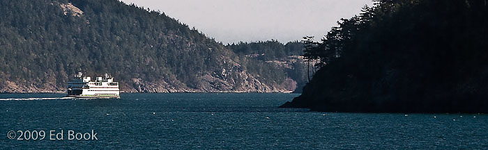 a ferry is transiting between two mountainous islands in Washington state's San Juan Islands.