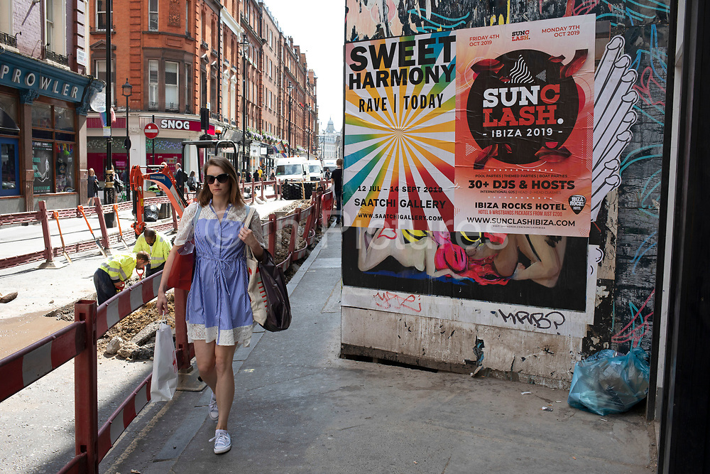 Woman walking past road works and advertising posters on Brewer Street in Soho, London, United Kingdom.