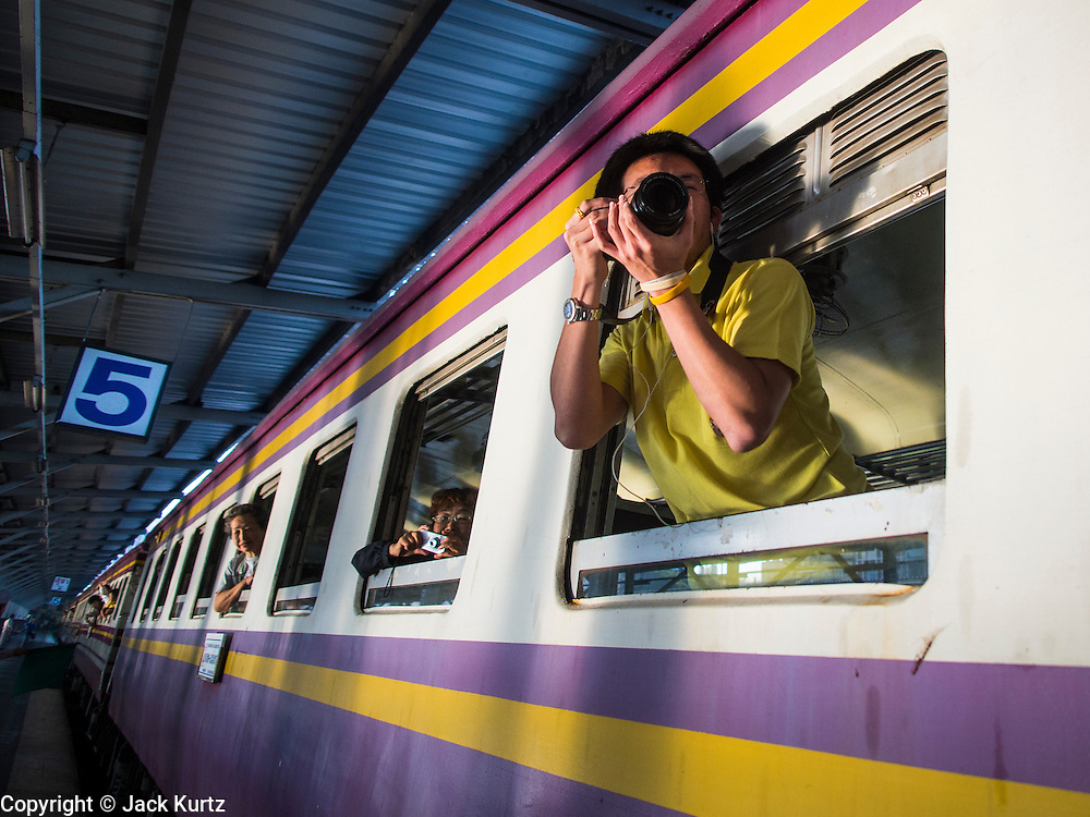 """05 DECEMBER 2013 - BANGKOK, THAILAND:  People lean out the window of a special steam engine train leaving Hua Lamphong Train Station on the 86th birthday of Bhumibol Adulyadej, the King of Thailand. Dec. 5, the King's Birthday, is a national holiday in Thailand, and is also celebrated as the country's """"Fathers' Day."""" The State Railways of Thailand put on special trains to take people to the King's """"Summer Palace"""" in the oceanside community of Hua Hin where the King granted a public audience. There were also merit making ceremonies throughout the country.  Many people wear yellow on the King's Birthday because yellow is the color associated with his reign. As of 2013, he was the longest reigning monarch in the world.          PHOTO BY JACK KURTZ"""