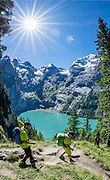 Above the beautiful lake of Oeschinnensee, easily reached by lift from Kandersteg, is a challenging hike traversing steeply up over Hohtürli Pass then down to Griesalp in the remote valley of Kiental, Switzerland, Europe. Ascend 1120 meters and descend 1380 m in 13 km, which feels much longer due to steep, exposed rocky & gravelly slopes. Stairs and ladders assist your footing. Optionally stay overnight in Blüemlisalp hut at Hohtürli Pass. This image was stitched from multiple overlapping photos.