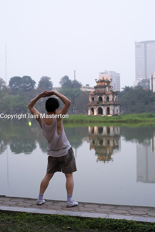 Evening Tai Chi exercises at Hoan Kiem Lake in Hanoi Vietnam
