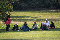 © Licensed to London News Pictures. 15/09/2020. London, UK. A group of woman relax in the shade on Primrose Hill in North London as large parts of the UK experience warm conditions. New Coronavirus restrictions introduced today prevent people from gathering in groups of more than six. Photo credit: Ben Cawthra/LNP