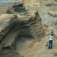 Tourists snap a selfie amidst eroded sandstone rocks on the southeastern coast of Oahu, Hawaii;