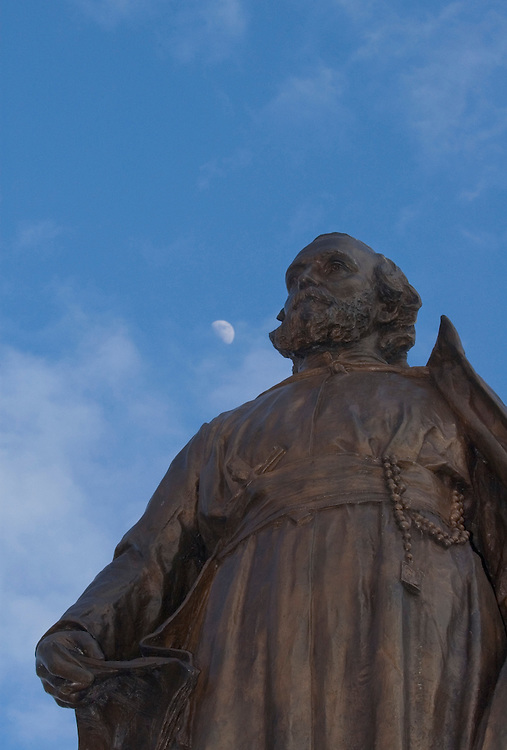 A statue of 17th-century French Jesuit explorer Father Jacques Marquette is seen in Marquette, Michigan with a half moon.