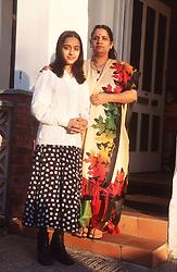 Portrait of mother and teenage daughter standing on doorstep,