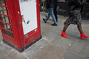 Red high heeled boots walking past a telephone box in London, United Kingdom.