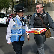A demonstrator offers a police liason officer donuts on the go. An unscheduled demonstration against the newly elected Conservative govenment makes it's way through Central London past Downing Street several times. After 5 years of coalition rule with severe austerity policies the Conservative party led by David Cameron won the general election and the demonstrators fear another 5 years of cuts. The Protest went on peacefully but loud closely followed by the police.