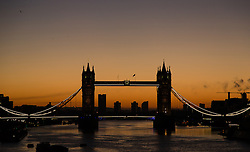 © Licensed to London News Pictures. 29/12/2013. London, UK. Orange sky behind Tower Bridge in London ahead of sunrise on a clear winter morning. Weather forecasts predict a dry and bright Sunday before more strong wind and heavy rain moves in early next week. Photo credit : Vickie Flores/LNP