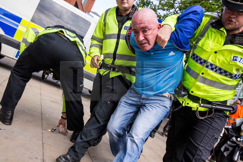 """© Licensed to London News Pictures . 22/08/2015 . Manchester , UK . A far-right protester is detained . Far-right nationalist group , """" North West Infidels """" and Islamophobic , anti-Semitic and white supremacist supporters , hold a rally in Manchester City Centre . Photo credit : Joel Goodman/LNP"""