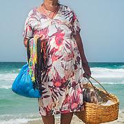 Maria Hernandez tiene 50 años trabajando en playa Parguito. Vende Rosarios (300mil), Escapularios (200mil), Tortugas, Virgenes y Pulseritas (100mil), collares de gomita a 250mil. Trae con ella 100 objetos y vende por dia alrededor de 300mil bsf en temporada baja y 500bsf en alta. Trabaja de 10:30am o mediodia a 5pm. Todos los dias de la semana. A veces usa protector.
