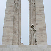 The twin white pylons of the Canadian National Vimy Memorial dedicated to the memory of Canadian Expeditionary Force members killed in World War one. At the front is a a figure of a weeping woman or better known as Mother Canada mourning her dead.  The monument is situated at a 100 hectare preserved battlefield with wartime tunnels, trenches, craters and unexploded munitions. The memorial designed by Walter Seymour Allward opened in 1936.