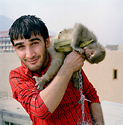 "Mustafa, aged 19 (although he is unsure of exact age) is a labourer on the Turquoise Mountain project rebuilding the old town centre, Murad khane. He is single and lives with his parents. The monkey is called Shadi. <br /> <br /> ""Before Turquoise Mountain came here it was very bad. Everywhere smelt, it was full of rubbish and the sewage – people just threw it out in front of their houses-   it was two or three metres high, you could reach the top floor of the houses by standing on the garbage.  During the war, there was nobody to clean up the rubbish, then buildings would collapse and then rubbish would go on rubbish. <br /> Before working with Turquoise Mountain I was just polishing shoes, now I get $5 dollars a day."""