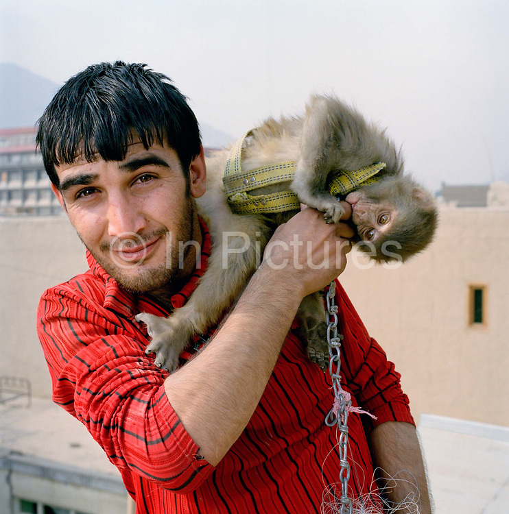 """Mustafa, aged 19 (although he is unsure of exact age) is a labourer on the Turquoise Mountain project rebuilding the old town centre, Murad khane. He is single and lives with his parents. The monkey is called Shadi. <br /> <br /> """"Before Turquoise Mountain came here it was very bad. Everywhere smelt, it was full of rubbish and the sewage – people just threw it out in front of their houses-   it was two or three metres high, you could reach the top floor of the houses by standing on the garbage.  During the war, there was nobody to clean up the rubbish, then buildings would collapse and then rubbish would go on rubbish. <br /> Before working with Turquoise Mountain I was just polishing shoes, now I get $5 dollars a day."""""""