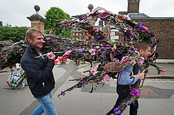 © London News Pictures. 23/05/2015. London, UK. Two man carrying a floral design. Members of the public carry exhibitors' plants from the 2015 Chelsea Flower show, which ends today (Sat). The Royal Horticultural Society flagship flower show has been held at the Royal Hospital in Chelsea since 1913. Photo credit: Ben Cawthra/LNP