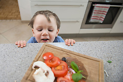 Boy looking at chopped vegetables in kitchen