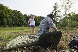 Young couple setting up tent in a forest, Bavaria, Germany