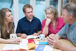 Younger couple giving pension advice to their middle aged parents,