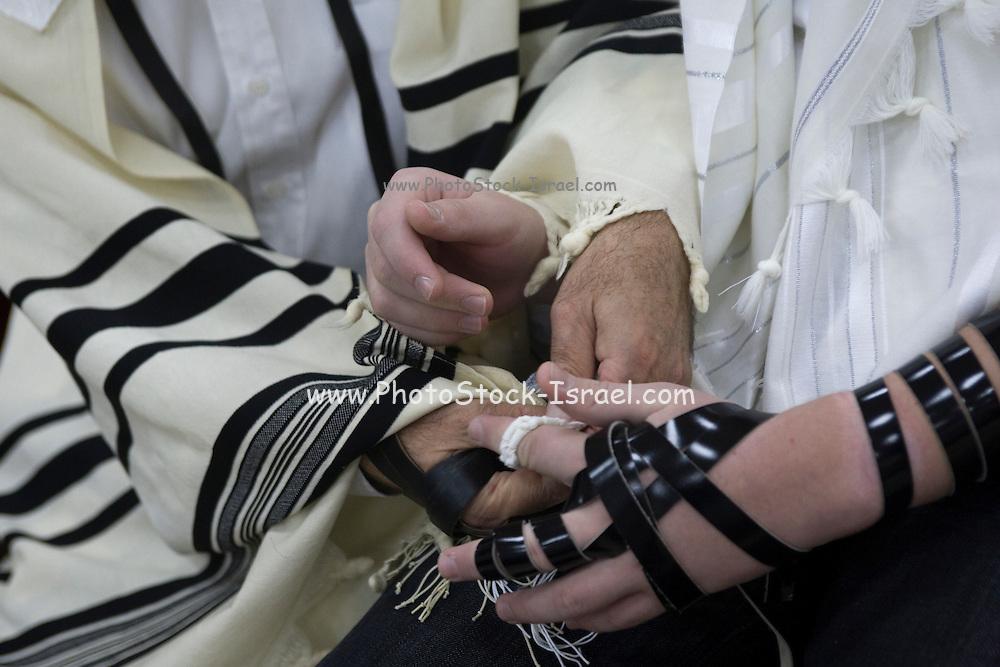 Israel, Tel Aviv, Beit Daniel, Tel Aviv's first Reform Synagogue Bar Mitzvah ceremony. Bar Mitzvah boy laying tefillin (phylacteries) during ceremony
