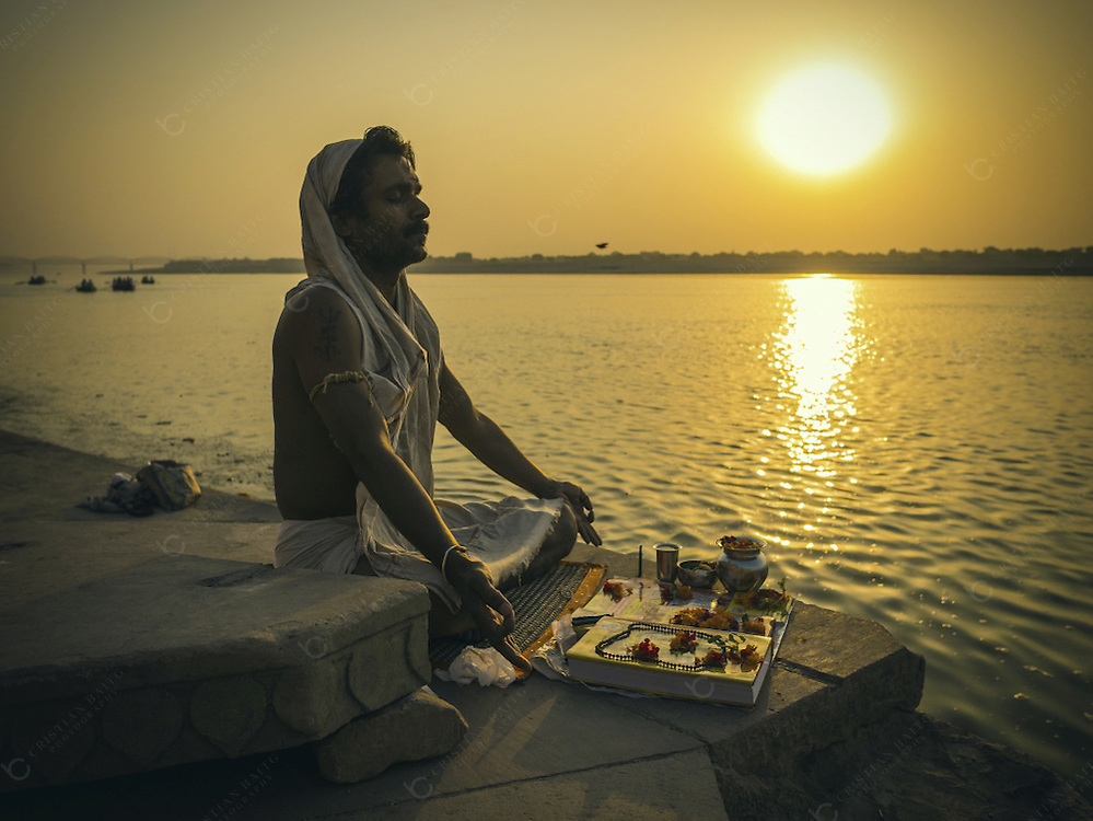 Varanasi, India - October 10, 2015 Man meditating in lotus pose at the Ganges river in one of the ghats in Varanasi India. The river is considered holy by Hindus. It is venerated as Goddess Ganga and bathing in their waters is considered a ritual that offers respect to the Goddess and internal purification. If this ritual is done in Varanasi it is even more powerful as this is the holiest city of the Jain and Hindu religion.