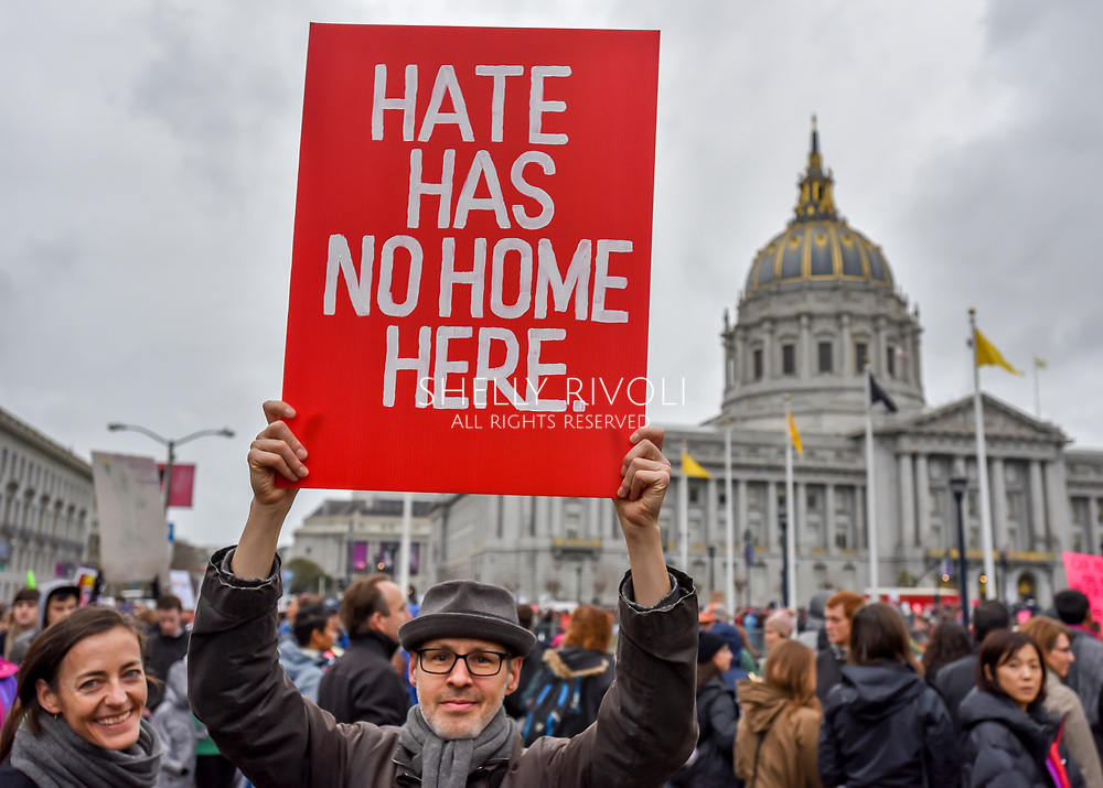 """In the crowd gathering at Civic Center Plaza before the Women's March, a man holds a bold red sign reading, """"Hate has no home here."""""""